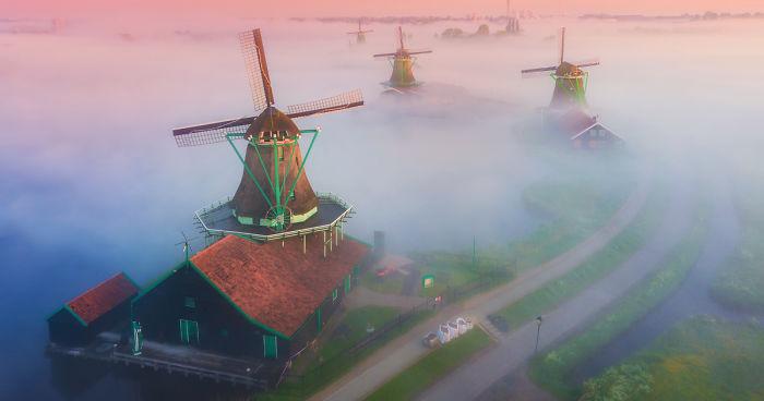 Fotografei moinhos de vento holandeses no nevoeiro e os resultados são mágicos